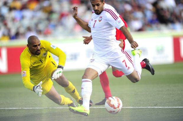 Right, United Arab Emirates player Ali Ahmed Mabkhout and Bahrain goal keeper Sayed Mohamed Abbas in action.