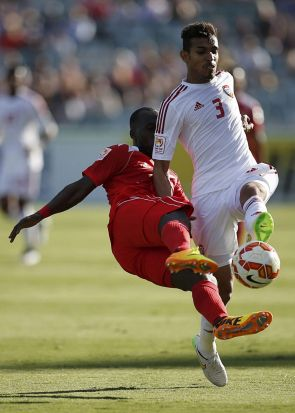 Bahrain's Abdulla Omar (L) fights for the ball against UAE's Walid Abbas.