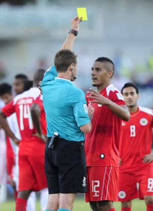 Right, Bahrain player Faouzi Aaish is given a yellow card after a tackle on United Arab Emirates goal keeper Majed Naser.