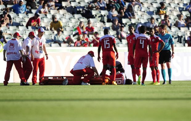 Bahrain player Mohamed Duaij Mahorfi is stretched off the field.
