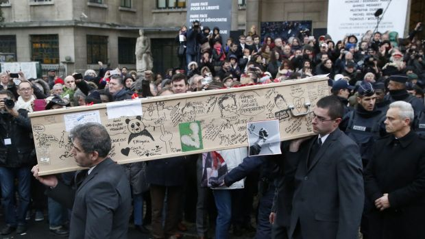 Pallbearers carry the casket of Charlie Hebdo cartoonist Bernard Verlhac, known as Tignous, decorated by friends and ...