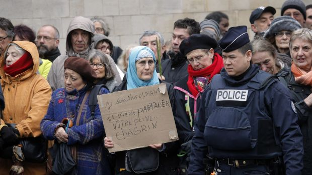 "A woman holds a board reading: "" I am muslim, I am here to share your pain"" as she waits to enter at the Pere Lachaise ..."