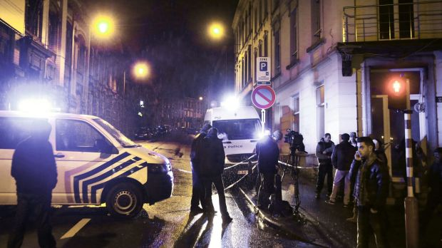 Journalists and residents stand near police vehicles as police set a large security perimeter in the city center of ...