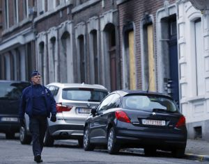 A Belgian police officer walks past the charred exterior of a house with boarded up windows in Verviers.