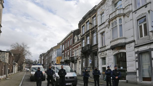 Belgian police arrested 13 people during a dozen raids overnight. Here police officers guard a street in Verviers, Belgium.