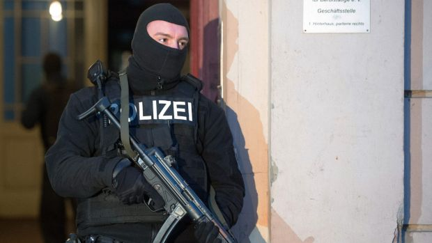 A member of a police task force stands in front of an apartment building where a raid took place against suspected ...