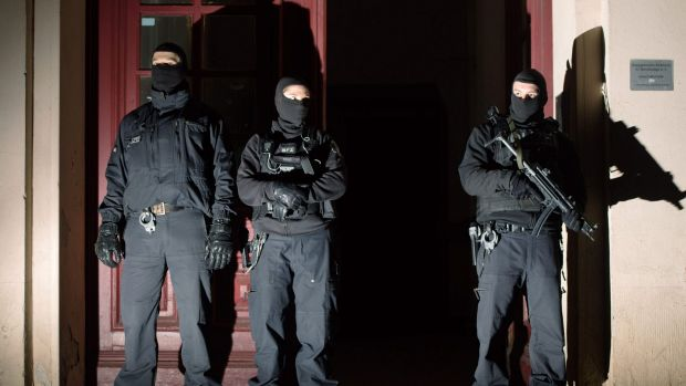Special police force guards the entrance of a house in Berlin as police raids several residences in Berlin on suspicion ...