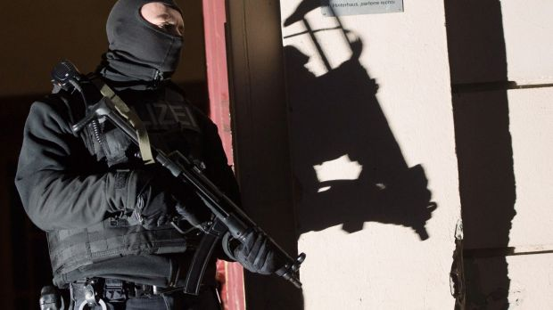 Special police force guards the entrance of a house in Berlin during an anti-terrorism raid.