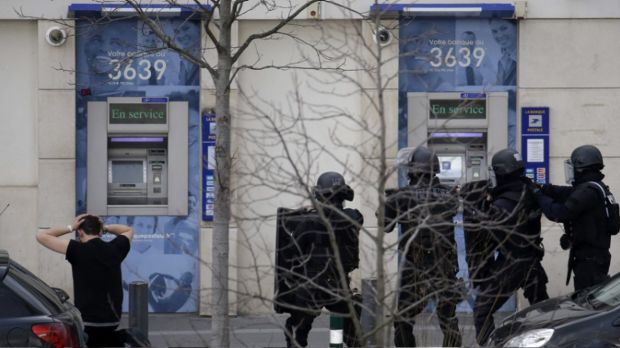 A suspect is detained by special police forces as a hostage situation is resolved at the post office in Colombes, near Paris