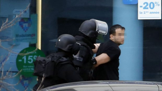 A man (right), who had allegedly taken two hostages in a post office, is arrested by French Research and Intervention ...