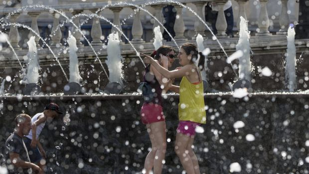 Girls cool off in a fountain  in Alexandrov Garden at the Kremlin Wall in Moscow, Russia on July 30, 2014.