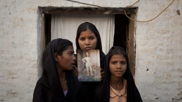 Fate altered: The daughters of Asia Bibi, pictured here in 2010, pose with an image of their mother.
