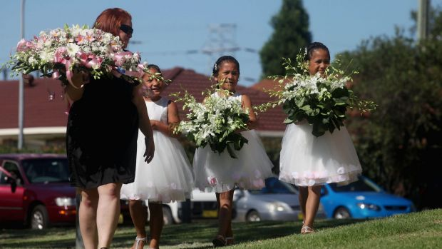 Triplet sisters of Tateolena carry flowers to the funeral.
