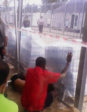 Two men reach for bottled water after the detainees blocked the compound gate.