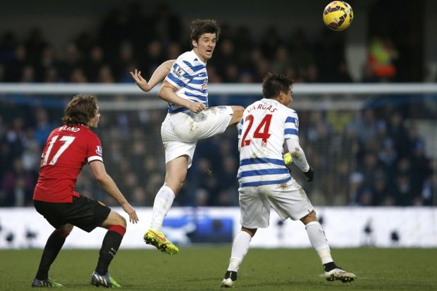 Heads up: Queens Park Rangers midfielder Joey Barton jumps for the ball against Manchester United at Loftus Road Stadium ...