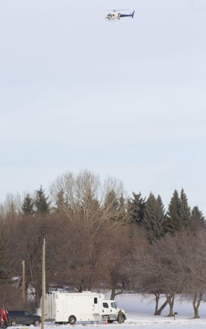 Police use a helicopter to search for the Alberta gunman, who was later found dead.