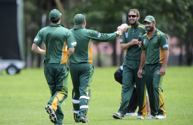 Second from right, Weston Creek bowler, Blake Dean is congratulated after taking a wicket.