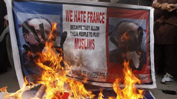 Posters featuring France's President Francois Hollande are set alight during anti-Charlie Hebdo protests in Quetta, ...