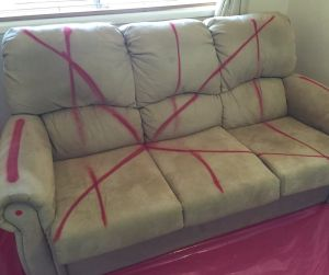 Red spray paint has been applied to a sofa in a Mr Fluffy house.