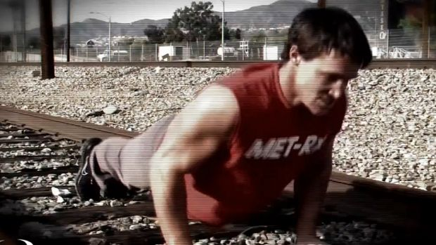 A screenshot from a Greg Plitt fitness video showing him working out on train tracks.