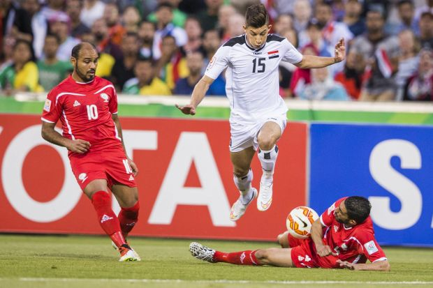 Dhurgham Ismael of Iraq dodges a tackle from a palestinian defender.