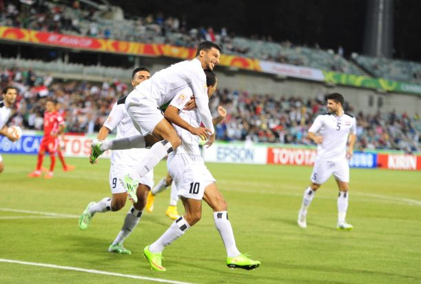From left, Iraq players Salam Shakir celebrates with Younus Mahmood after he scores the first goal for Iraq.