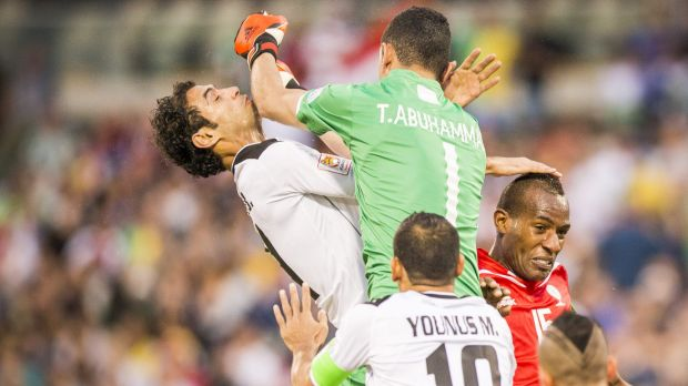Tawfiq Abuhammad of Palestine give Saad Abdulameer of Iraq an elbow to the face while challenging for the ball.