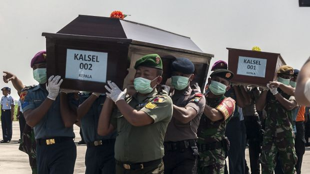 Indonesian police and military personnel carry coffins with the remains of a passengers of the AirAsia flight 8501 in ...