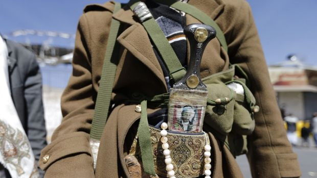 A Houthi fighter wears a traditional dagger (Jambiya) with a picture of a slain comrade on it as he poses for a photo ...