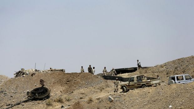 Houthi fighters walk at a presidential guards' barrack on a mountain overlooking the presidential palace in Sanaa.