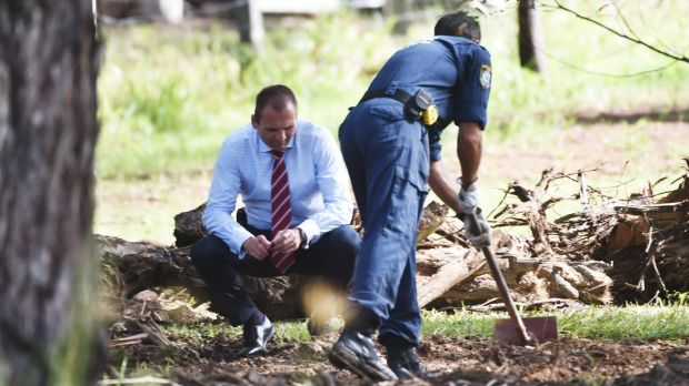 Police search the grounds of the semi-rural property in Bonny Hills.