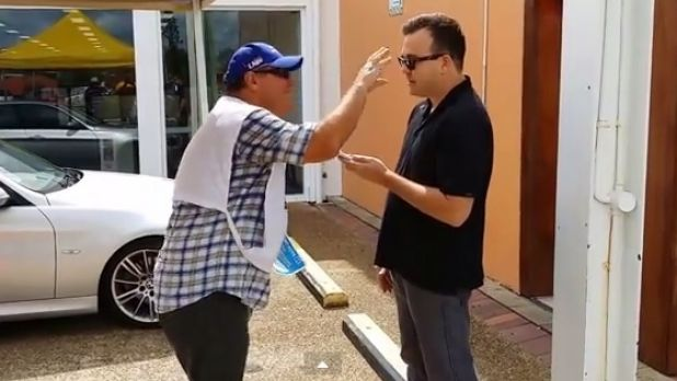 LNP MP Ray Stevens dances and flaps in front of a reporter on the Gold Coast.