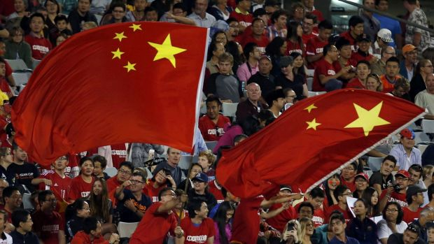 China's fans wave giant national flags during their Asian Cup Group B soccer match against North Korea in Canberra on ...