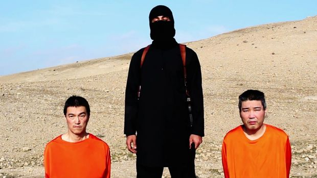 Deadline looms ... An IS militant with the two Japanese hostages, journalist Kenji Goto, left, and military contractor ...