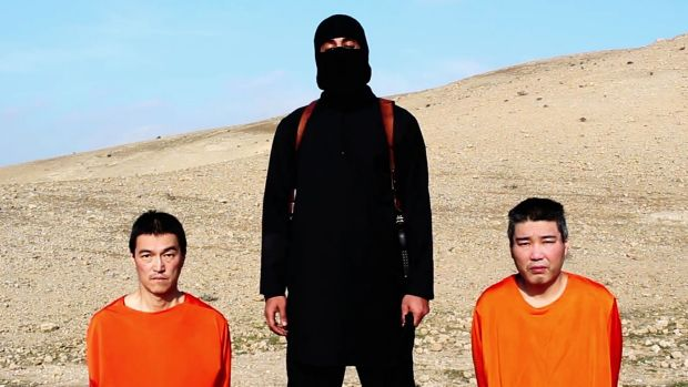 An IS militant with the two Japanese hostages, journalist KenjiGoto Jogo, left, and military contractor Haruna Yukawa.