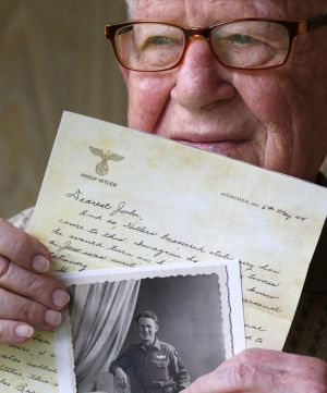 Danny Jacobson holds a photo copy of a letter written on Adolf Hitler's stationary with a photo of himself in uniform in ...