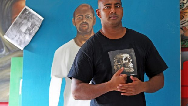 """Myuran Sukumaran, in front of a self-portrait, has improved rapidly.  """"Every visit ... I find he's made more remarkable ..."""