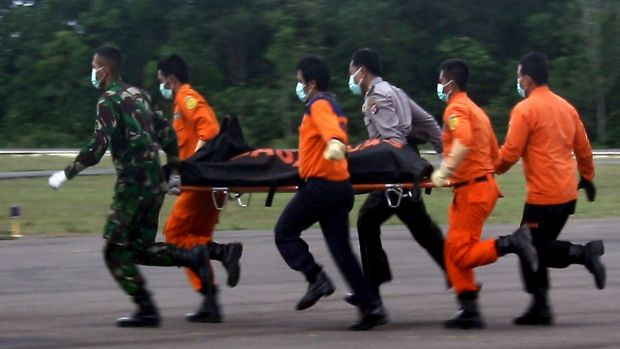Rescue personnel unload body bags containing bodies recovered from the underwater wreckage of AirAsia flight QZ8501.