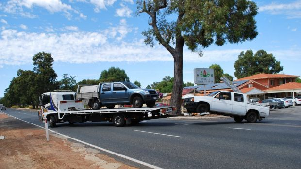 Vehicles linked to the roof-fixing scam are removed from Hazelmere's Banksia Tourist Park.