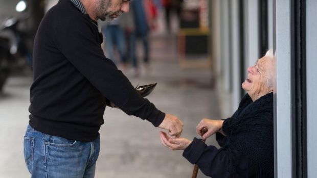 An elderly lady begs for money on the streets of Athens.