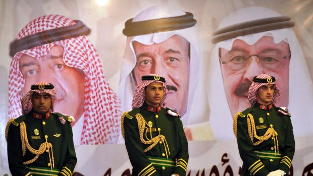 Saudi royal guards stand on duty in front of portraits of the late King Abdullah (right), his successor King Salman ...