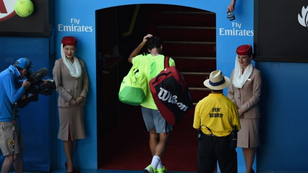 The vanquished: holding his head, Roger Federer makes his way off the court.