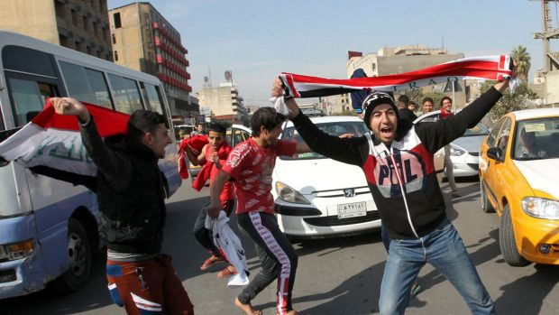 Something to really cheer about ... Iraqi men celebrate the Asian Cup victory in the streets of Baghdad.