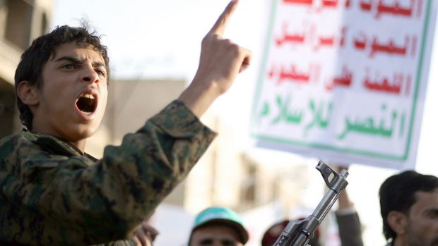 An armed member of the Shi'ite Houthi movement shouts during a demonstration to support the movement's uprising in the ...
