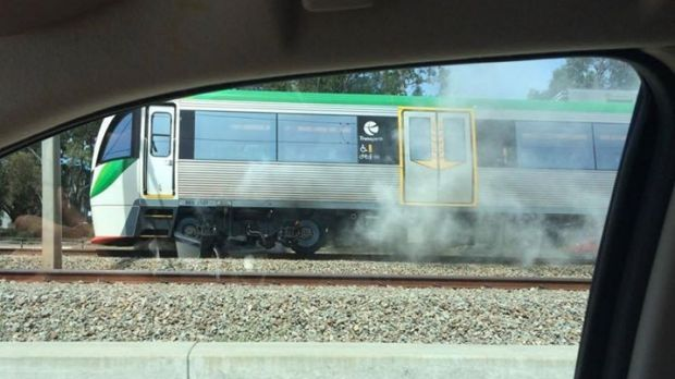 Smoke billows from beneath the train.