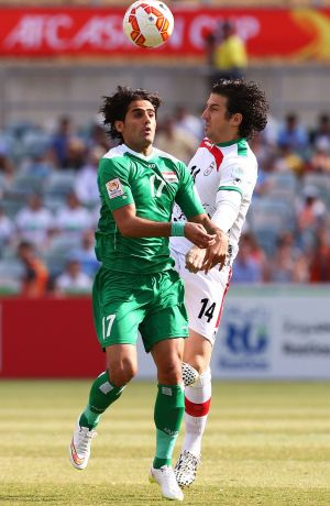 Controversy: Alaa Abdulzehra, left, and Iran's Andranik Teymourian clash during Friday's Asian Cup quarter-final.