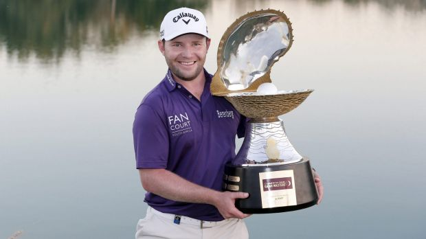 Branden Grace of South Africa poses with the trophy after the final round of the Qatar Masters at the Doha Golf Club on ...