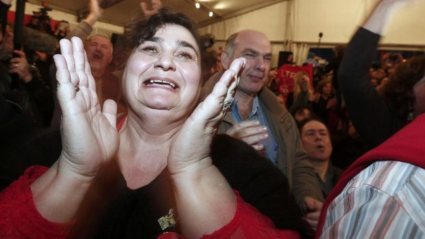 A Syriza party supporter cheers as exit polls announce that party leader Alexis Tsipras is on the brink of victory.