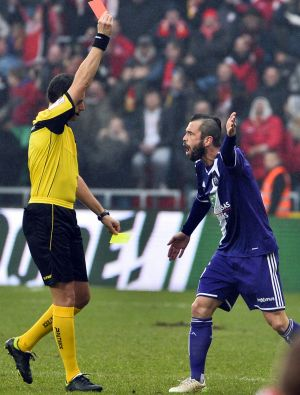 Steven Defour is sent off after kicking the ball at the home fans.