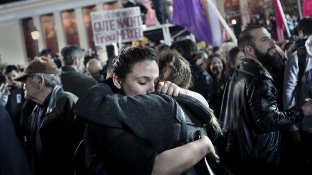 "Syriza supporters embrace after the results are announced. A sign in the background says ""Good night Mrs Merkel"" in German."
